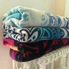 Three colorful towels folded on white wicker stand