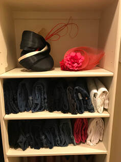 Closet shelves: two shelves of jeans folded vertically. Top shelf with decorative hats.