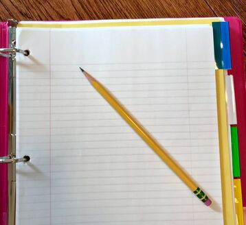 Pink binder with lined paper, colorful dividers, and a pencil